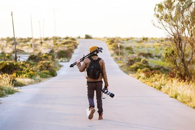 彼の肩とカメラを手に三脚で砂漠の道を歩く若い写真家 Premium写真