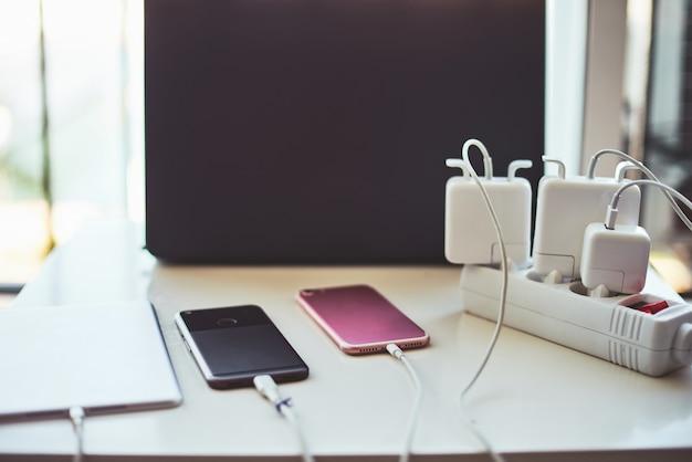 電話の充電器とラップトップのテーブル Premium写真