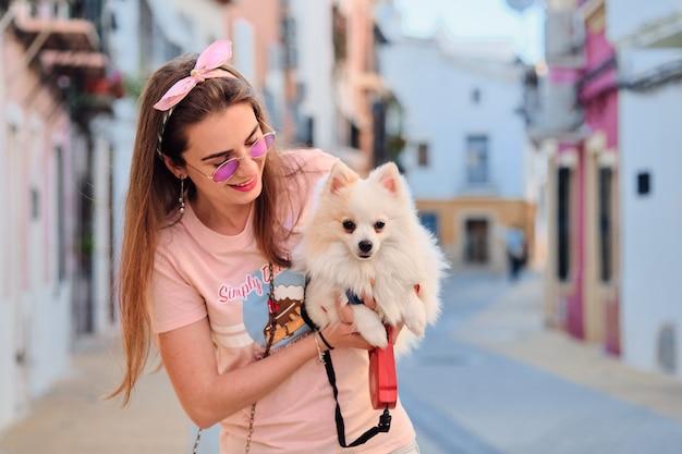 白いふわふわポメラニアンと歩いている若い女の子の肖像画。 Premium写真