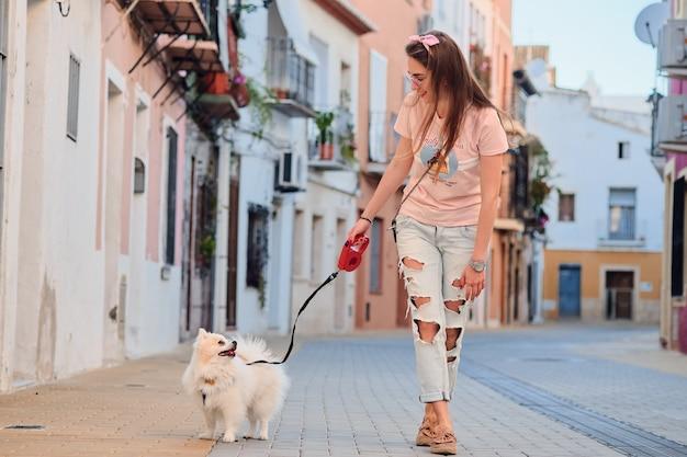 白いふわふわポメラニアンと歩く少女。 Premium写真