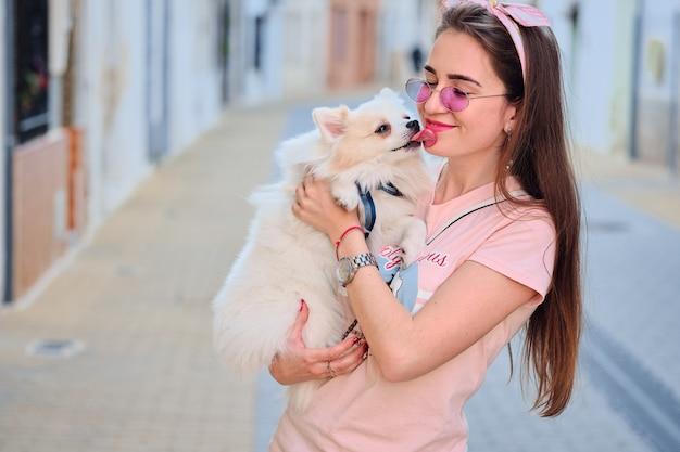 Портрет белой пушистой померанской собаки лижа лицо молодой девушки. Premium Фотографии