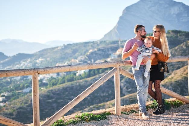 晴れた日を楽しんでいるかわいい男の子と幸せな若い家族 Premium写真