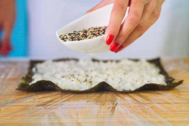 日本の寿司を埋める女性シェフの手は、海苔シートにご飯とごまを巻きます。 Premium写真