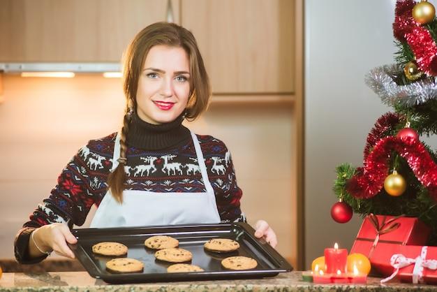 クリスマスツリーの近くに焼きたてのチョコレートクッキーを保持している若い幸せな女 Premium写真