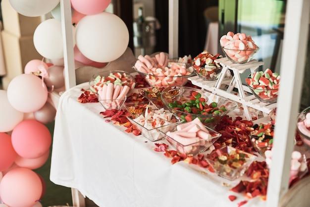 キャンディーバーにピンクのマシュマロやその他のお菓子。 Premium写真