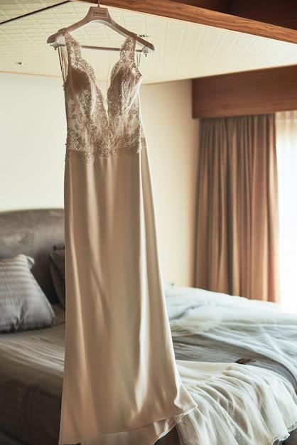 高級ホテルの部屋の天井にぶら下がっているウェディングドレス。 Premium写真