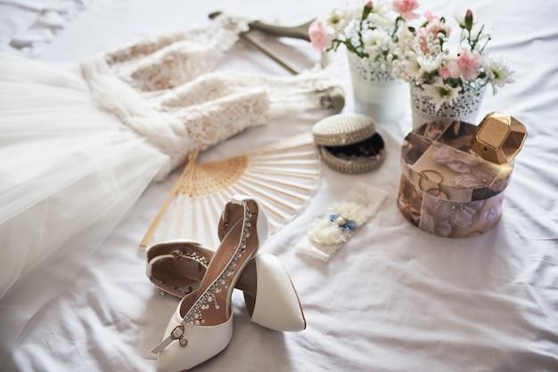 スタイリッシュな白いウェディングブライダルシューズ、ドレス、香水、花、白のジュエリー Premium写真
