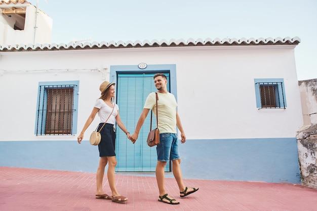 歩いて旅行者の幸せな若いカップル Premium写真