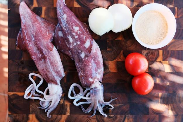 木製の背景に野菜とイカ Premium写真