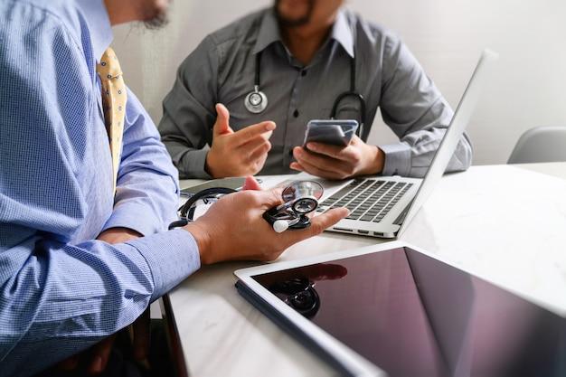 スマートフォン現代デジタルタブレットラップトップコンピューターで働く医師 Premium写真