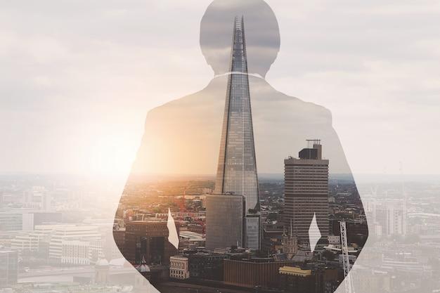 Двойная экспозиция бизнесмена успеха используя смартфон с лондонским зданием, эффект фильтра Premium Фотографии
