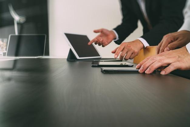 共同作業チーム会議のコンセプト、近代的なオフィスにスマートフォンとデジタルタブレットとラップトップコンピューターを使用しての実業家 Premium写真