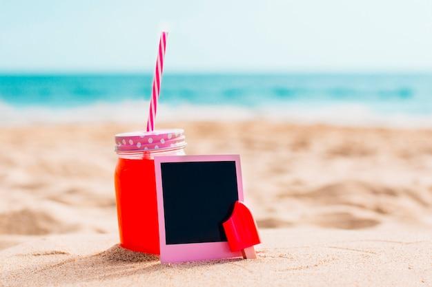 ビーチでスムージーとピンクのインスタント写真 無料写真