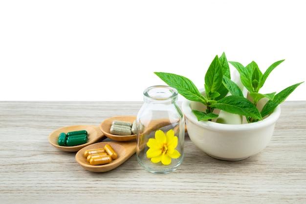 Травяная капсула из трав природы для хорошего здоровья, дополнения таблетки на деревянный стол Premium Фотографии