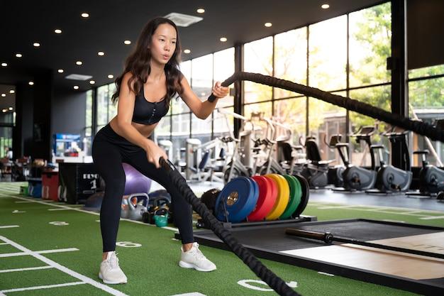 ジムでの戦いのロープを持つ若いアジア女性 Premium写真