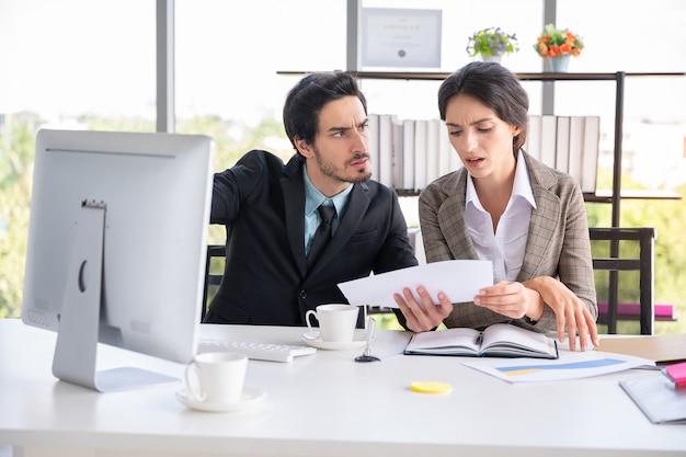 ビジネスの男性と女性のオフィスで紙の文書を探しています Premium写真