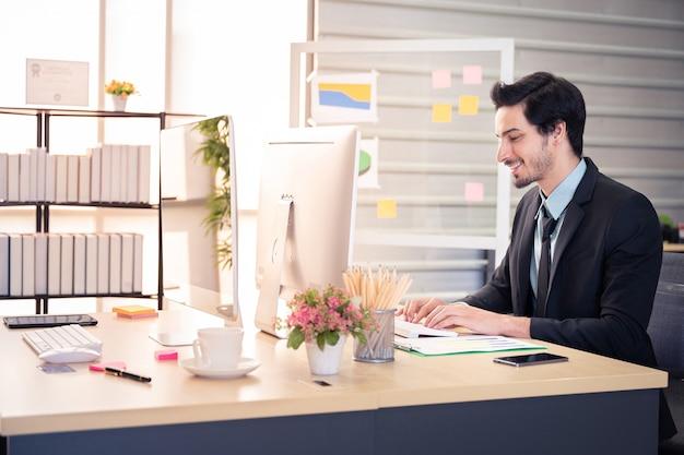 幸せの実業家とオフィスのコンピューターでの作業中に笑顔 Premium写真