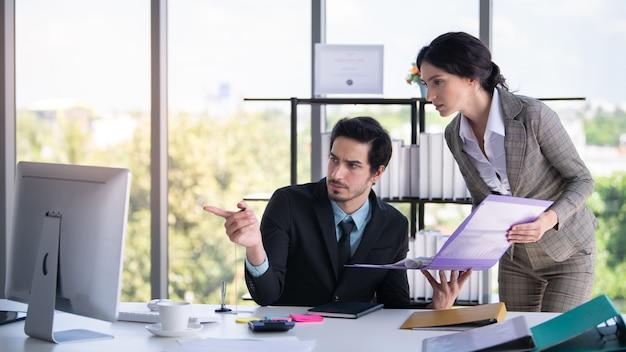 ビジネスマンおよび女性探しているとオフィスでラップトップを指す Premium写真