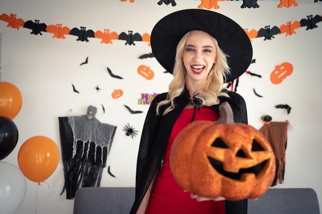 パンプキンパーティーを自宅で保持している魔女服の若い白人女性 Premium写真