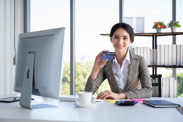 近代的なオフィスにクレジットカードを保持しているビジネス女性の肖像画 Premium写真