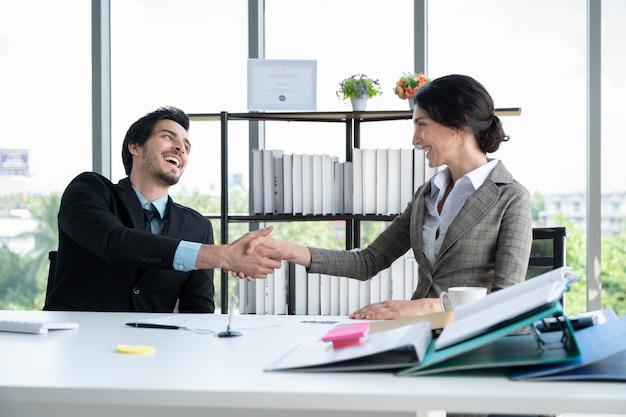 金融事務所で働くビジネスマンと握手の女性の肖像画 Premium写真
