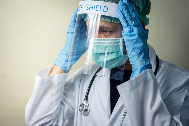 顔面シールドと聴診器で制服を着ているアジアの男性医師 Premium写真