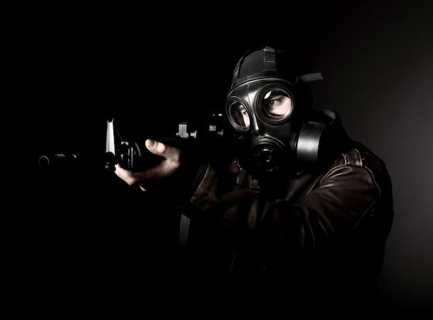暗闇の中で防毒マスクを持つテロリスト Premium写真