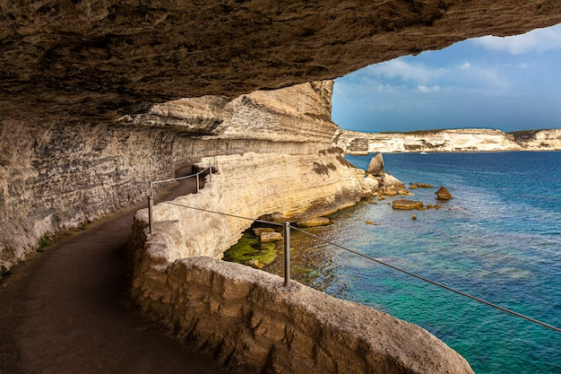 Живописная тропа высечена в скале, которая проходит вдоль моря в городе бастия на корсике Premium Фотографии