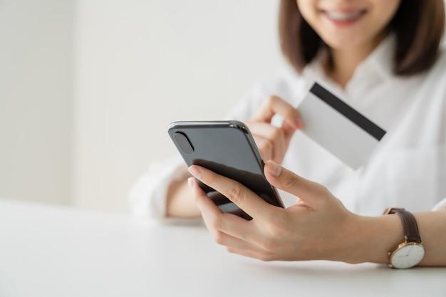 スマートフォンでクレジットカードと支払いをオンラインで保持している女性。 Premium写真