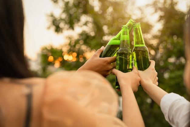 Счастливая молодая группа друзей вечеринки и напитки. Premium Фотографии