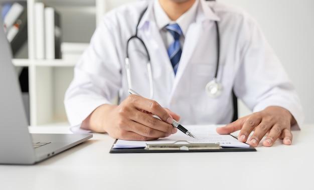 Доктор, держа файл отчета пациента для оценки симптомов на столе. Premium Фотографии