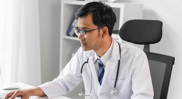 Врач с помощью ноутбука и глядя на файл отчета пациента для оценки симптомов на столе. Premium Фотографии