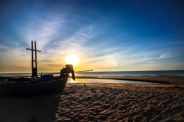 シルエットボートとビーチの美しい日の出 Premium写真