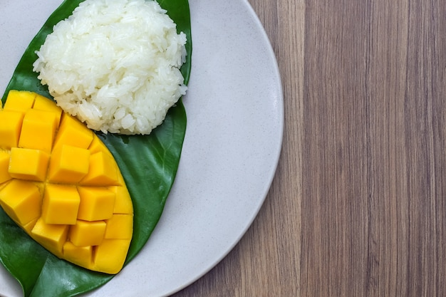 木製テーブルの上のもち米と美しい黄色のマンゴーを彫るのクローズアップマクロ撮影皿 Premium写真