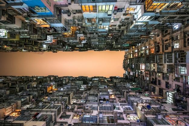 香港、クォーリーベイの古いコミュニティの混雑した住宅タワーの低角度のビュー。混雑した狭いアパートの風景、高い住宅密度と住宅ブルースの現象。 Premium写真