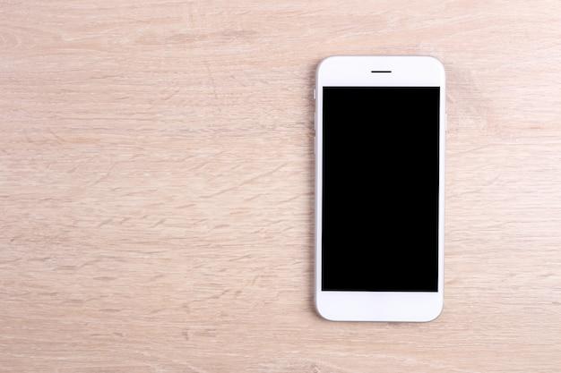 木製の背景にモックアップ画面のスマートフォン Premium写真