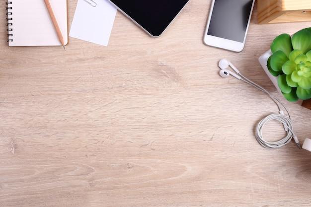 スマートフォン、タブレット、事務用品の木製の背景 Premium写真
