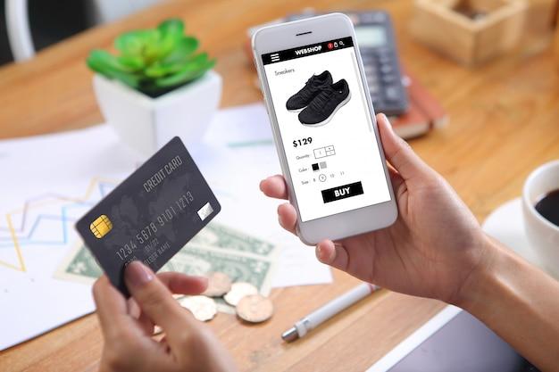 Женщина с помощью кредитной карты для покупки черных кроссовок на сайте электронной коммерции через смартфон с листом бизнес-отчета и канцелярских принадлежностей на деревянный стол Premium Фотографии