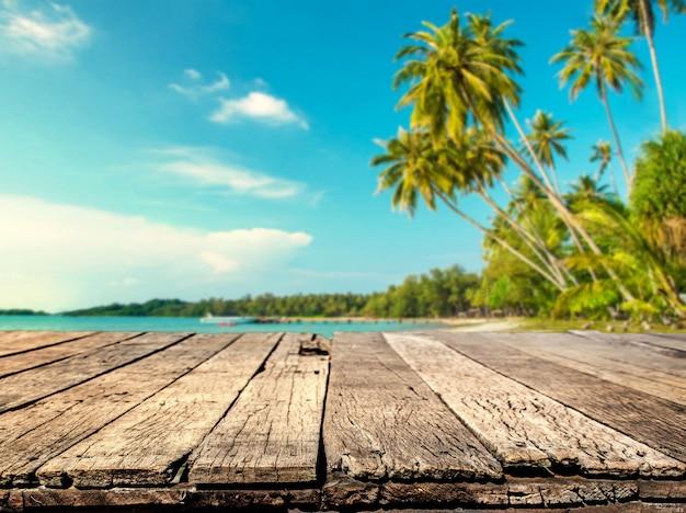 ぼやけた海とココナッツの木の背景の木のテーブル Premium写真