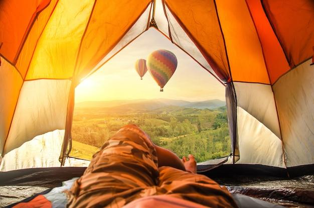 日の出で美しい熱気球と霧を探している旅行者。 Premium写真