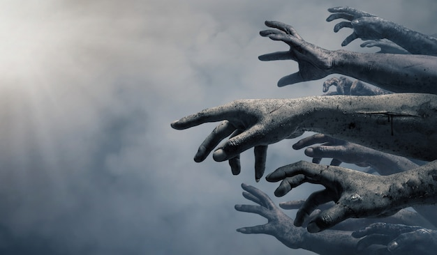 暗いハロウィーンの夜に上昇しているゾンビの手。 Premium写真