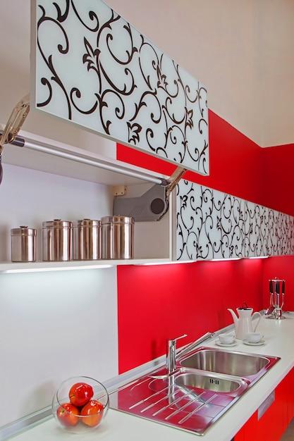 赤い装飾が施されたモダンな電化製品を備えた豪華な新しい赤いキッチン Premium写真