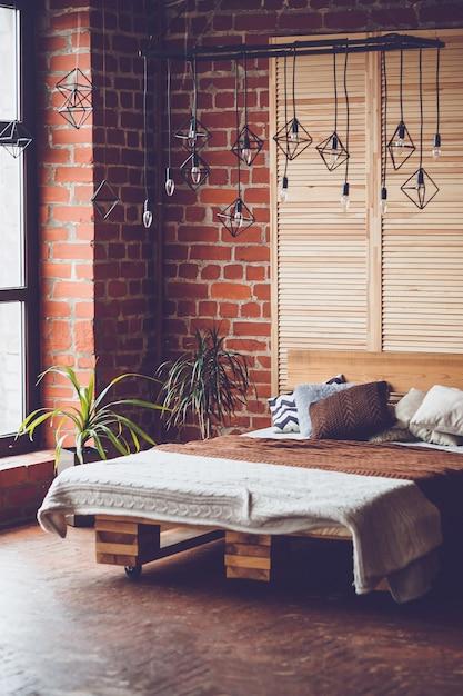 ダブルベッド、赤レンガの壁、大きな窓のあるシンプルなベッドルーム Premium写真