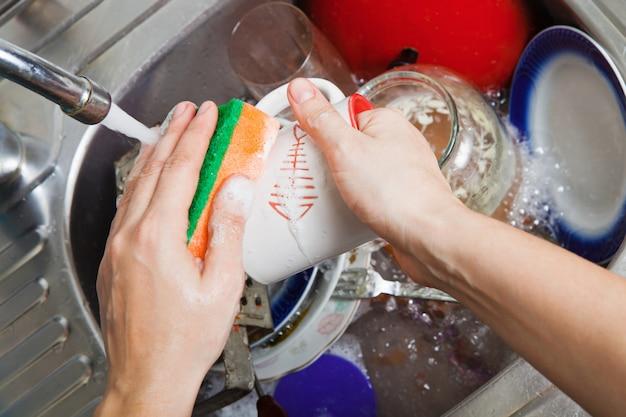 女性が台所で食器を洗います Premium写真