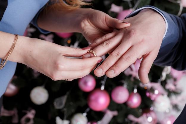 花嫁は結婚式の日に新郎の指にリングを着ています。愛、幸せな結婚の概念。 Premium写真