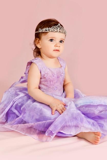 美しい少女は、ピンクのティアラ、紫色のドレスと一緒に座っています。 Premium写真
