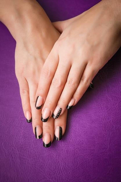 Женские руки с черным маникюром на фиолетовый Premium Фотографии