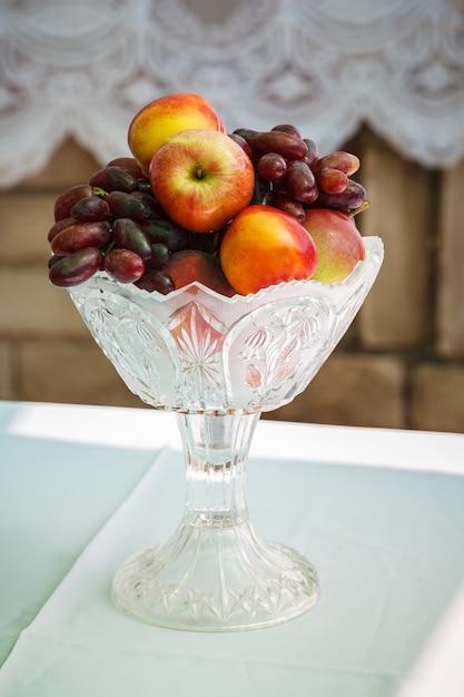 明るく熟したフルーツ-ブドウとネクタリンテーブルの上の花瓶に Premium写真