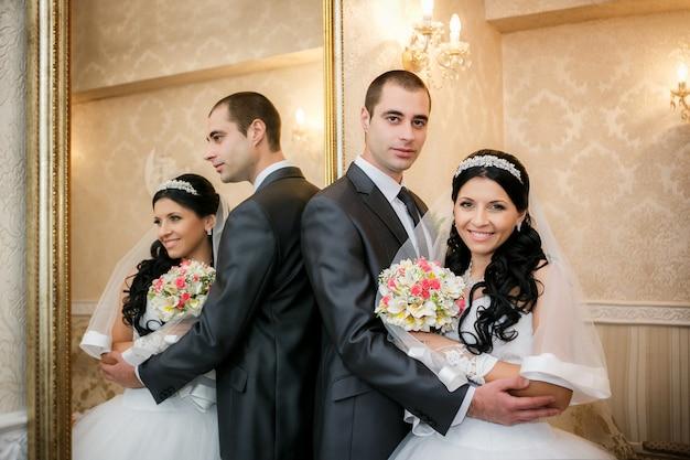 幸せな新郎と新婦は鏡の近くに立って、それに反映されます Premium写真