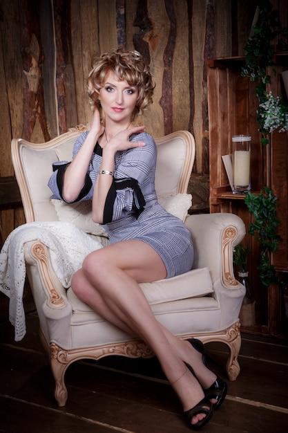 肘掛け椅子に座っている美しい女性 Premium写真